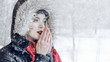 Outdoor close up portrait of young beautiful girl walking on the winter street. Model warming hands. Snowfall effect.