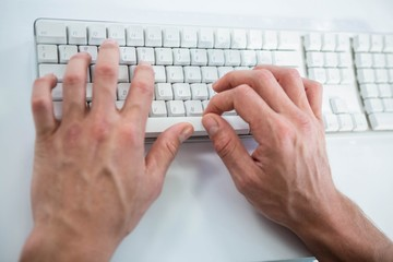 Close up view of a male hand typing on keyboard