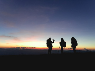 Silhouettes of group hikers people with backpacks enjoying sunset view from top of a mountain. Travel concept, Vintage filtered image.