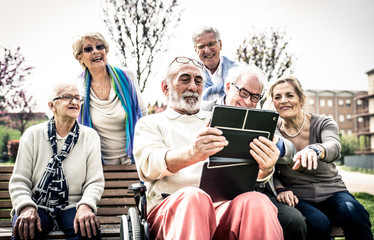 Group of senior looking funny videos on a digital device