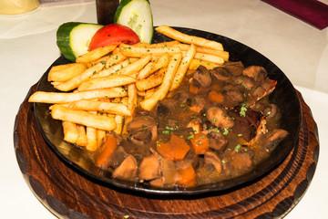 Grillfleisch mit Pilzsoße und Pommes Frites, serviert in einer