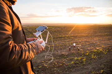 Demonstration of  copter. Man controls quadrocopter flight. Flying the copter over a field. Remote control in a man's hands.