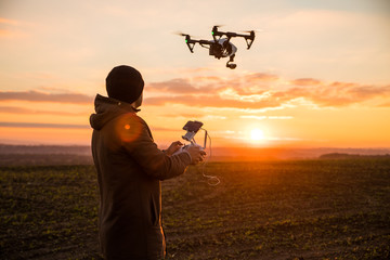 Man operating a drone with remote control. Dark silhouette against colorful sunset. Soft focus. Wall mural