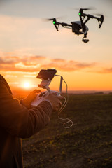 Man controls the fly of quadrocopter in field over sunset background
