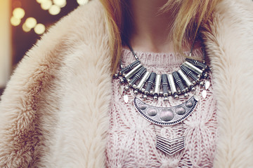 Elegant winter outfit. Close up of massive necklace. Boho style. Fashionable girl on the street. Female fashion. City lifestyle. Toned