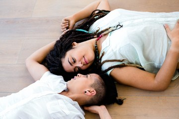 Lesbian couple lying on wooden floor