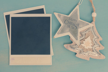 Blue and white christmas with stras and instant photo on blue wooden background, vintage style, retro toned