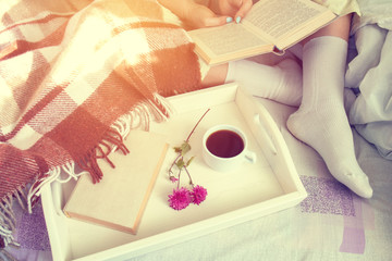 Women sitting on bed with book near tray with old book, tangerines and cup of coffee, cozy home concept. Coloring and processing photo with soft focus in instagram style.