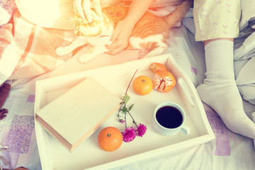 Women sitting on bed with red cat near tray with old book, tangerines and cup of coffee, cozy home concept. Coloring and processing photo with soft focus in instagram style.