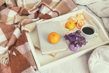 Breakfast in bed. Old book, tangerines and cup of coffee in tray, cozy home concept. Coloring and processing photo with soft focus.