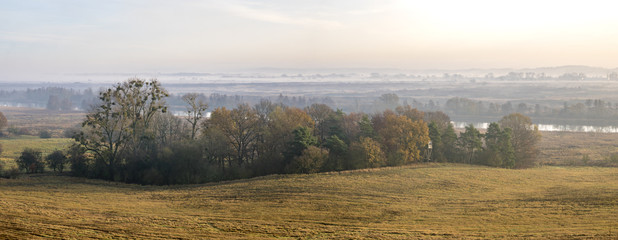 misty autumn morning over the valley, hunting tower on the edge