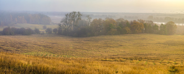 misty autumn morning over the valley, hunting tower on the edge of the forest