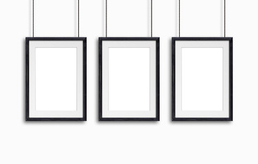 Three black wooden frames, hanging on cords