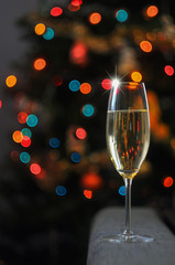 glass with champagne against the background of the shining garland