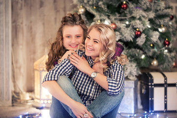 mother and the daughter celebrate Christmas in the cozy house with a fireplace and a fir-tree. Holiday Christmas and new year