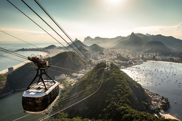 Wall Mural - View of Rio de Janeiro city from the Sugarloaf Mountain by sunset with a cable car approaching