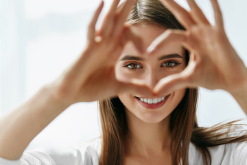 Beautiful Happy Woman Showing Love Sign Near Eyes. Fototapete