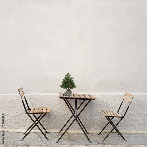 table christmas tree and two chairs near the wall at