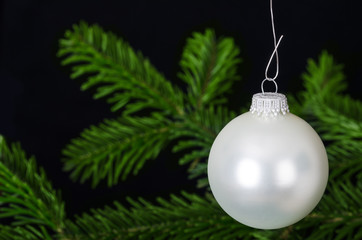 White silver bauble, a spherical Christmas ornament, usually hung on Christmas tree.  Christmas ball, a Xmas tree decoration in front of fir branch. Front view macro object photo on black background.