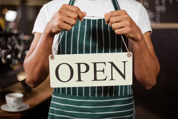 Mid section of barista holding open sign