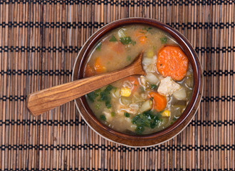 Chicken, barley and vegetable soup in ceramic bowl with wooden spoon on bamboo placemat