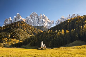 Church in valley surrounded with mountains, Italy