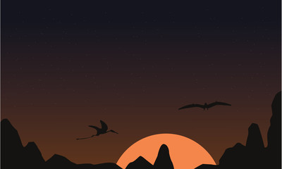 At sunset pterodactyl landscape of silhouettes