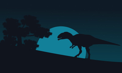 Silhouette of mapusaurus on hill at night
