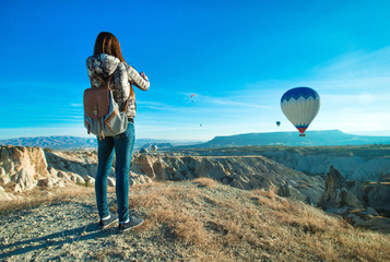 Female tourist taking photos of hot air balloon in Cappadocia