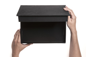Two hands hold a empty(blank) black gift box and open isolated white