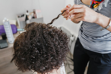 Close up of a hairdresser curling short black hair with hair irons.