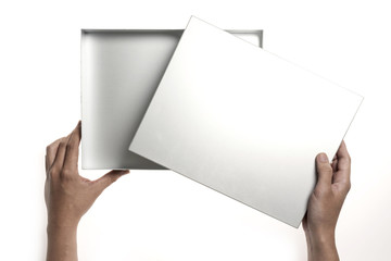 Two hands hold a empty(blank) silver(stainless) gift box isolated white