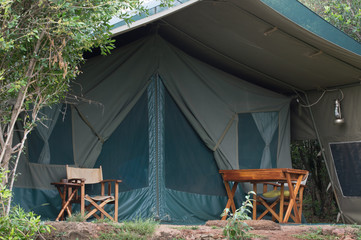 The exterior of a canvas safari tent with two chairs and a desk on the porch in the Masai Mara. Photographed in natural light in Kenya Africa.