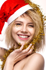 Jolly cheerful beautiful girl in a New Year's image with a festive make-up, wearing a Santa Claus with a smile. The beauty of the face. Photos shot in the studio.