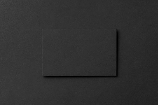 Mockup of blank business card at black textured background.