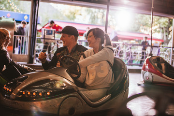 Friends on bumper car ride in amusement park