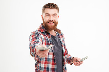 Happy bearded man in plaid shirt giving money on camera