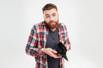 Upset young man holding empty wallet