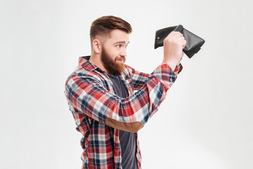 Young man in plaid shirt looking inside his empty wallet
