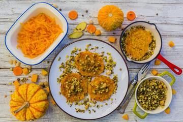 Fried fritters with pumpkin with fried sprouts and spices on wooden background. Vegetarian food.