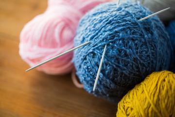 close up of knitting needles and yarn balls