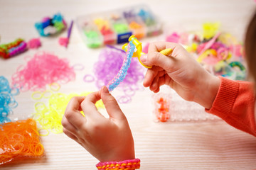 hands weaving of rubber band bracelet, closeup, wooden background