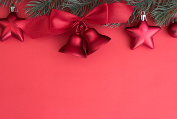 Red Christmas bells ornament decorate on fir tree with red backg