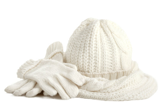A white knitted hat, scarf and gloves  isolated on white background.