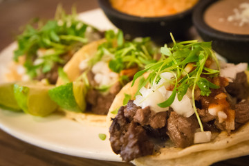 Plate of three street style tacos topped with micro greens, onions, chives and various sides