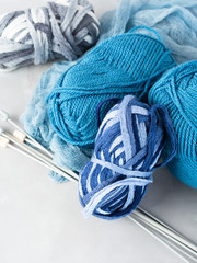 Woolen yarn with knitting needles. Vertical.