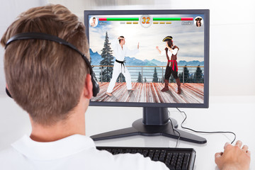 Man Playing Fighting Game On Desktop