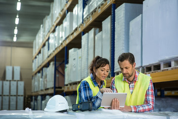 Man and a woman have short meeting in a warehouse and checking inventory levels of goods. First in first out, Last in last out, team working together concept photo.
