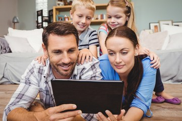 Parents holding digital tablet while kids sitting on their back