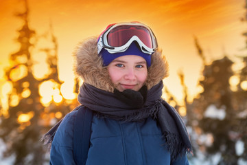 Portrait of a young girl in a hood and ski mask on the background of a sunset in the winter in the mountains. Red skin on the face of a teenager in very cold weather. Frozen woman in warm clothes